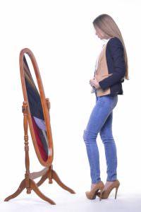 鏡の前で服装をチェックする女性
